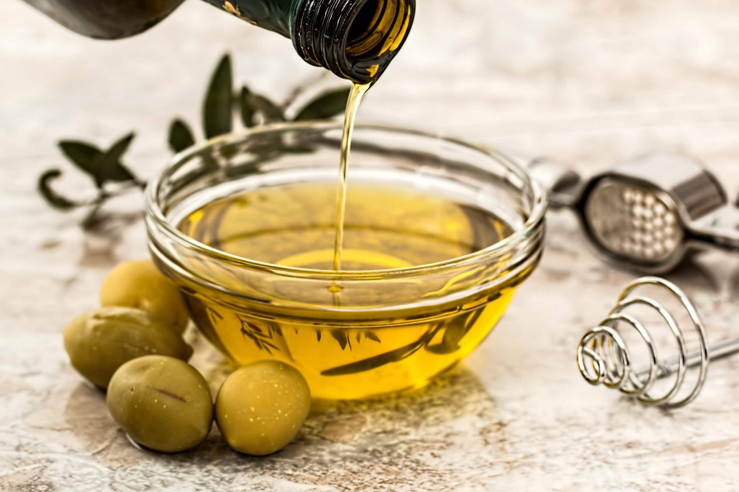 fles olijfolie in schaaltje en olijven ernaast
